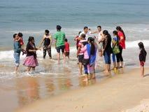 Touristes indiens les balançant pieds sur la plage de Candolim Photographie stock libre de droits