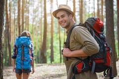 Touristes joyeux marchant dans la forêt Photographie stock libre de droits