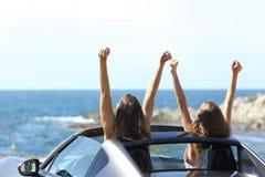 Touristes joyeux observant la mer dans une voiture convertible Image libre de droits