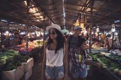 Touristes marchant entre les rangées sur les jeunes du marché exotique tropical choisissant des fruits frais et des légumes dans  photo libre de droits