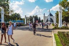 Touristes marchant et faisant un cycle dans l'exposition d'Achi économique Image libre de droits