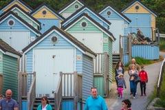 Touristes marchant parmi les huttes colorées de plage Image stock