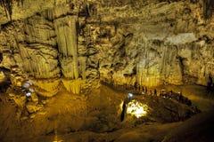 Touristes marchant sur la caverne de stalactites semblant infernale Image stock