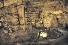 Touristes marchant sur la caverne de stalactites semblant infernale Images stock