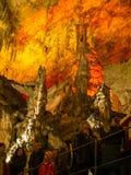Touristes marchant sur le chemin parmi les stalactites et les stalagmites lumineuses Photo stock