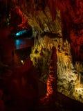 Touristes marchant sur le chemin parmi les stalactites et les stalagmites lumineuses Photos libres de droits