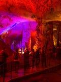 Touristes marchant sur le chemin parmi les stalactites et les stalagmites lumineuses Image libre de droits