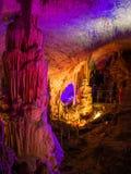 Touristes marchant sur le chemin parmi les stalactites et les stalagmites lumineuses Photo libre de droits