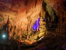 Touristes marchant sur le chemin parmi les stalactites et les stalagmites lumineuses Image stock