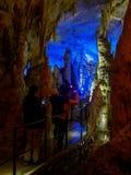 Touristes marchant sur le chemin parmi les stalactites et les stalagmites lumineuses Photos stock