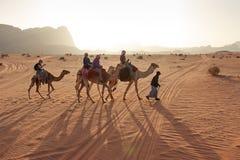 Touristes montant des chameaux au coucher du soleil dans le désert de Wadi Rum, Jordanie Photo stock