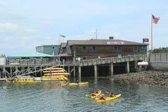 Touristes montant des kayaks de mer dans le port de barre Images libres de droits