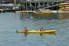 Touristes montant des kayaks de mer dans le port de barre Image libre de droits