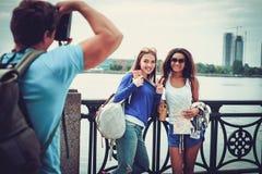 Touristes multi-ethniques d'amis prenant la photo près de la rivière dans une ville Images stock