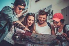 Touristes multiraciaux d'amis avec la carte Photographie stock libre de droits