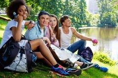 Touristes multiraciaux d'amis en parc Photos stock