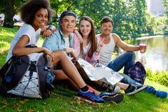 Touristes multiraciaux d'amis en parc Images stock