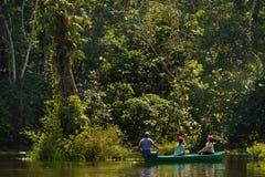 Touristes non identifiés barbotant un canoë dans Image libre de droits