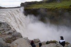 Touristes non identifiés observant Dettifoss étroitement en Islande Images libres de droits