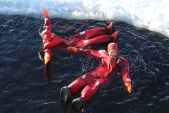 Touristes non identifiés adaptés avec un bain de glace de costume de survie en mer baltique congelée Image stock