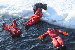 Touristes non identifiés adaptés avec un bain de glace de costume de survie en mer baltique congelée Images libres de droits