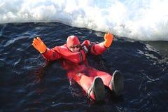 Touristes non identifiés adaptés avec un bain de glace de costume de survie en mer baltique congelée Image libre de droits