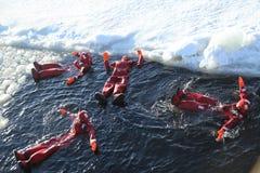 Touristes non identifiés adaptés avec un bain de glace de costume de survie en mer baltique congelée Photos stock