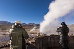 Touristes observant un geyser dans le domaine de del Tatio de geysers dans le désert d'Atacama, Chili du nord Images libres de droits
