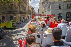 Touristes passant l'autobus de touristes de deux-plate-forme à Budapest Photographie stock libre de droits