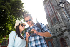 Touristes positifs employant l'appareil-photo de photo Images libres de droits