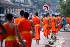 Touristes prenant à photos Laos les moines bouddhistes avec l'aumône bouddhiste donnant la cérémonie sur la route le matin, tradi photos libres de droits