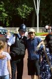 Touristes prenant des photos avec le policier Photos libres de droits