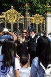 Touristes prenant des photos avec le policier Photo libre de droits