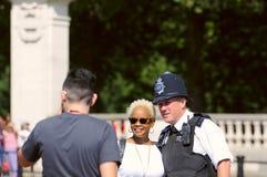 Touristes prenant des photos avec le policier Image stock