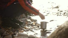 touristes prenant l'eau des lacs d'eau douce dans le pot pour faire cuire sur le feu clips vidéos