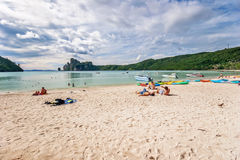 Touristes prenant un bain de soleil sur le sable d'une plage tropicale Images libres de droits