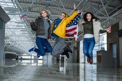 Touristes radieux sautant avec des drapeaux images stock