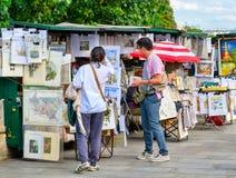 Touristes regardant les peintures typiques d'un artiste à Paris Images stock