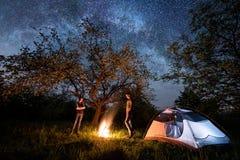 Touristes romantiques de couples se tenant à un feu de camp près de la tente sous des arbres et du ciel nocturne complètement des Photos stock