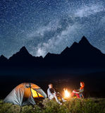 Touristes romantiques de paires s'asseyant par le feu de camp et la tente sous le ciel étoilé incroyablement beau et regardant en Photos stock