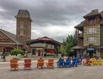 Touristes s'asseyant dans des recliners en bois colorés dans la station de vacances populaire canadienne bleue de village de mont Image stock