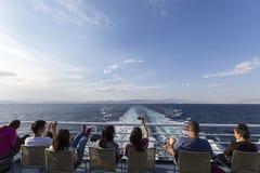 Touristes s'asseyant sur la plate-forme d'un bateau se dirigeant à l'isla de Santorini Photographie stock libre de droits