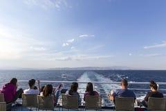 Touristes s'asseyant sur la plate-forme d'un bateau se dirigeant à l'isla de Santorini Photo libre de droits