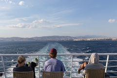 Touristes s'asseyant sur la plate-forme d'un bateau se dirigeant à l'isla de Santorini Photos stock