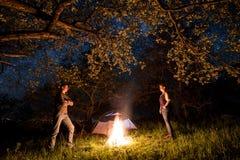 Touristes se tenant à un feu de camp près de la tente sous des arbres et du beau ciel nocturne complètement des étoiles Camping d Image libre de droits