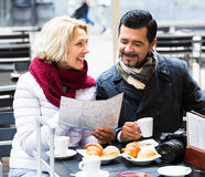 Touristes supérieurs lisant la carte au café Photographie stock libre de droits