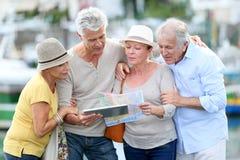 Touristes supérieurs regardant la carte et le comprimé en ville Photographie stock