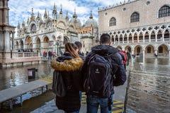 Touristes sur des panneaux de canard dans la place de St Mark inondé à Venise, Italie photographie stock libre de droits