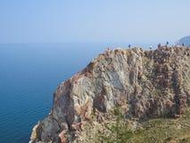 Touristes sur le dessus de la falaise de l'?le d'Olkhon Vue du lac Ba?kal image libre de droits