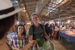 Touristes sur le marché en plein air tropical dans les fruits frais de achat et les légumes des jeunes de la Thaïlande Photo stock